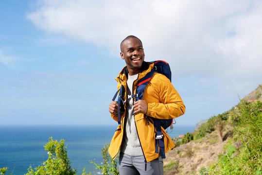 happy african american man with backpack in nature