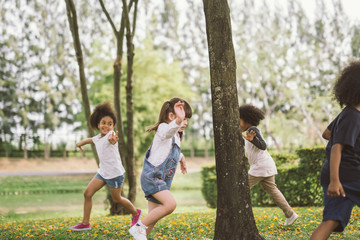 kids playing outdoors with friends. little children play at nature park.