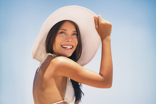 Beach hat Asian bikini woman enjoying sun wearing fashion white hat for solar protection skin care on summer vacation holidays. Young happy people lifestyle.