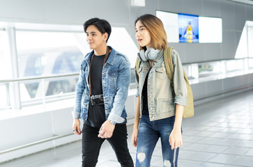 Young Asian travel couple walking around in Airport Lounge Happy Smile Man And Woman Flight Holiday Vacation Travel.Travelling concept.
