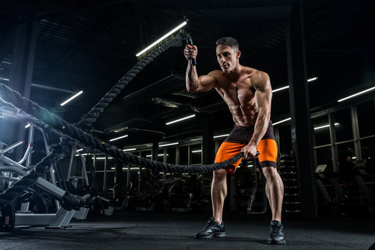 A young handsome bodybuilder doing a workout in the gym.