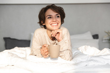 Smiling young girl relaxing in bed