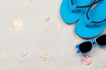 Blue flipflops on sandy beach, overhead