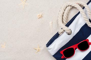 Beach bag on sandy beach, summer vacation background