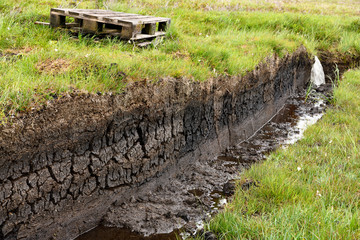 Trench cut into deep Peat of wetland moors on Isle of Skye Scotland to drain water for harvest