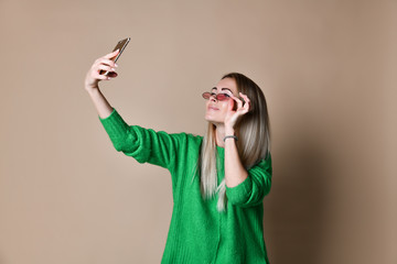 Close-up portrait of young cheerful fashion blonde woman in sweater wear makes selfie on smartphone, over beige background