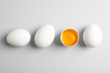 Chicken eggs and half with yolk on white background, space for text