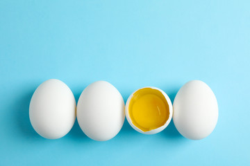 Chicken eggs and half with yolk on color  background, space for text