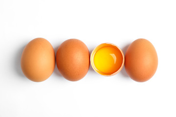 Chicken eggs and half yolk on white background, space for text