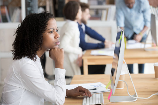 Serious black female employee thinking sitting in front of computer