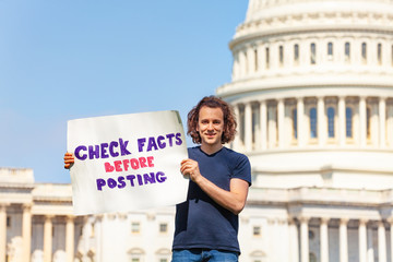 Protester holding sign check facts before posting