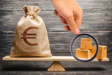 Magnifying glass is looking at a bag of euro money and a bunch of boxes on the scales. Economic relations between subjects, the global economic model. trade balance between countries, exchange