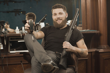 Enjoy your haircut. Portrait of a handsome professional barber posing with a Winchester gun in his barbershop