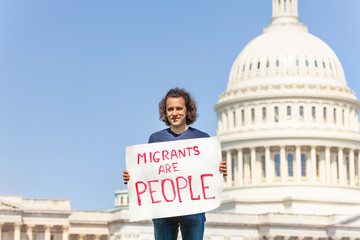 Protester holding sign migrants are people in hands