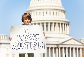 Protester holding sign I have autism in hands