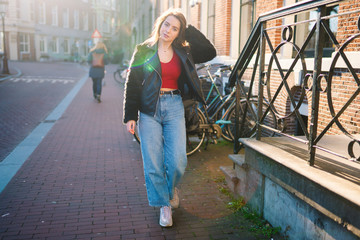 Portrait of a beautiful girl on a sunny day. Streets of Amsterdam. Great mood. A girl enjoys her lifestyle. She is wearing a red T-shirt, jeans and a leather jacket.