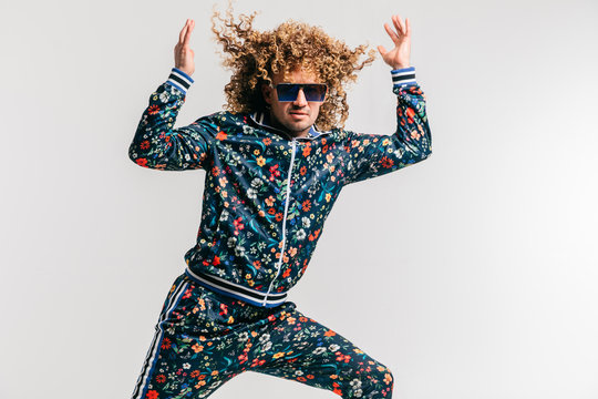 Excited adult funny man in stylish vintage clothes posing on white studio background. 80s fashion. Funky guy in tracksuit and sunglasses expressive indoor unusual portrait. Shouting cheerful male.