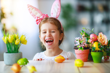 Happy easter! funny child girl with rabbit ears and eggs  .