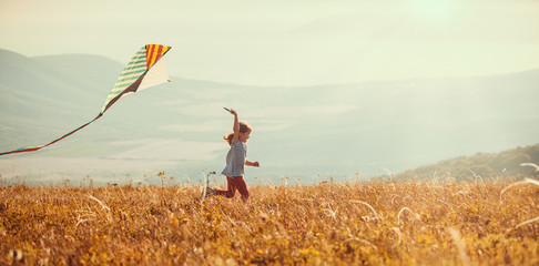 happy child girl running with kite at sunset outdoors.
