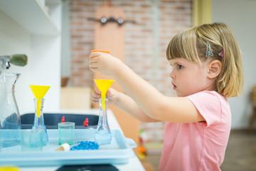 Little child performing experiment like scientist in pre-school
