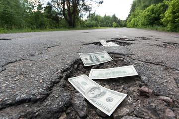 Dollar bills in the potholes on road