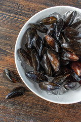Fresh seafood raw mussels on ice in bowl flat lay
