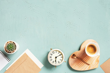 Blue textured background with cup of hot coffee and alarm clock