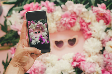 Hand holding phone and taking photo of pink heartshaped sunglassess in stylish pink and white peonies frame on pink paper flat lay. Instagram blogging. Summer vacation