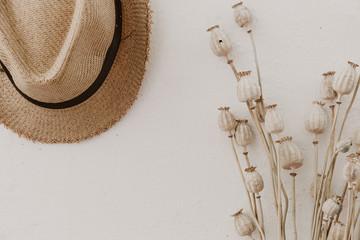 Straw hat with dried poppy, creamy background, minimal lifestyle