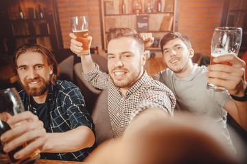 Taking selfie with your hand Three bearded friends having fun at bar, posing for photo, looking camera of smartphone