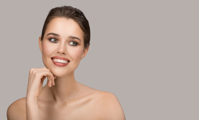 Wall Mural - Portrait of young woman. Perfect clean skin and beautiful smile. Gray background.