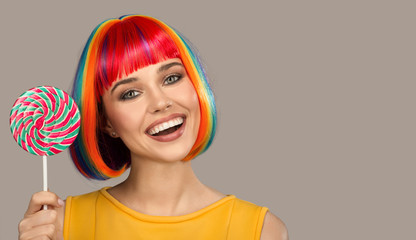Wall Mural - Cheerful smiling woman with bright colorful hair holding big lollipop.