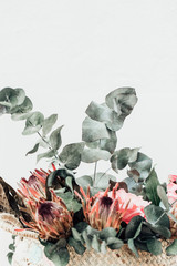 Minimal flower composition with rprotea and eucalyptus in bohemian style