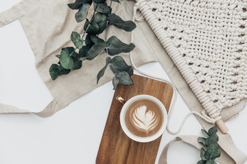 Fototapeta Flat lay Cup of coffee on wooden serving tray and eucalyptus branch with macrame decoration. Minimal bohemian lifestyle concept for blog and social media obraz