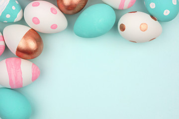 Easter corner border of pink, white, blue and rose gold Easter Eggs against a pastel blue background. Top view with copy space.