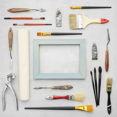 Paintbrushes, tubes of paints, palette knifes, artist canvas in roll, wooden frame, canvas stretcher pilers on marble background. Painters supplies. Top view.