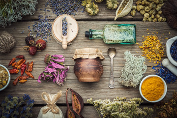 Dry medicinal herbs, plants, roots, ingredients for making herbal medicine drugs, bottle of infusion, jar of ointment, mortar on wooden background.