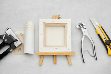 Artist canvas on wooden easel, canvas in roll, canvas stretcher pilers, knife and staple gun on marble background. Painters supplies. Top view.