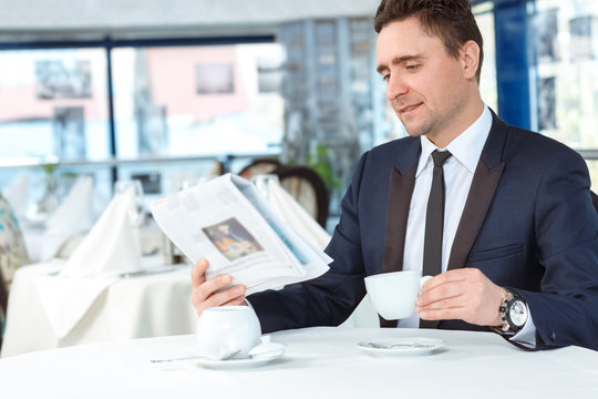 Pleasant start of the day. Portrait of a mature businessman having morning cup of coffee reading newspaper in a local cafe