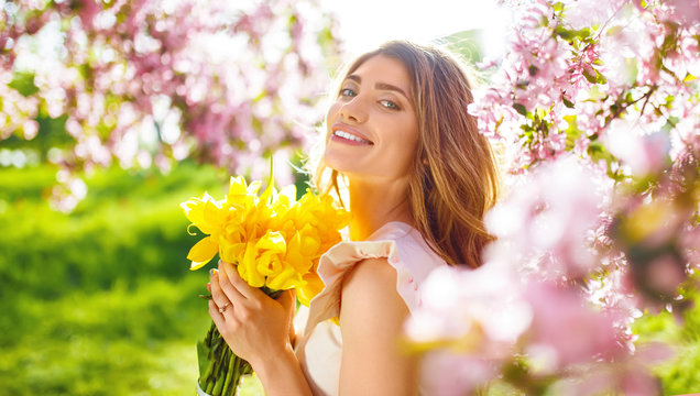 Beauty Portrait of Beautiful Young Brunette Woman In Nice Spring Dress With A Bouquet Of Tulips.Spring Style. Beautiful Spring Garden. Fashion Spring Summer Photo. Fashion and style concept. Long edge