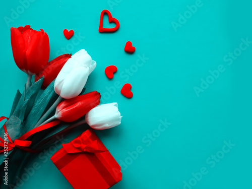 Bouquet of red and white tulips on bright blue background. Flat lay, copy space. Greeting card for Women's Day, Mother's Day or Valentine's Day