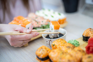 girl eating sushi set with chopsticks on restaurant