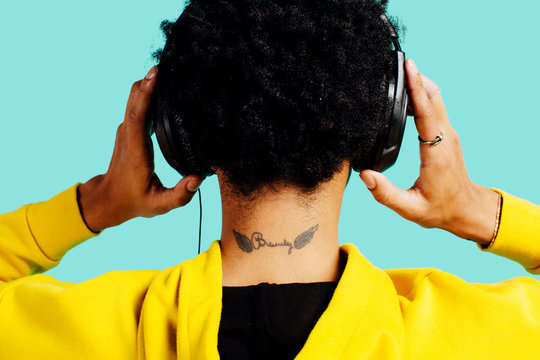 Portrait of the back of a young man's neck with tattooed wings and headphones