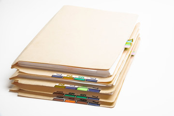 A stack of color-coded and numbered yellow file folders containing sheets of papers, files and documents set on a white background.