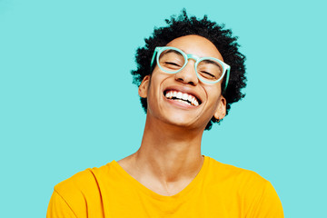 Portrait of a happy  young man isolated on blue background