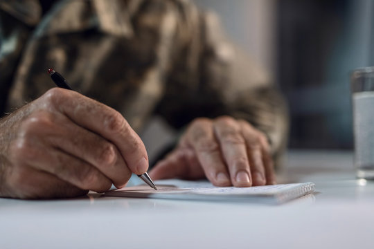 Close up of senior soldier taking notes.