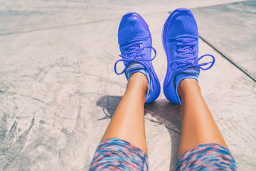 Running shoes fashion activewear healthy active people lifestyle. Selfie woman taking pictures of royal blue trainers during workout at gym floor outside.