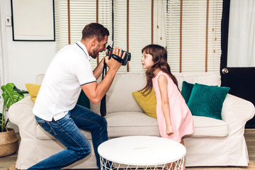 Father making photo his little daughter at home