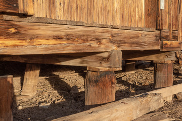 Construction detail of wood piers and beams supporting an old building, American Southwest, horizontal aspect