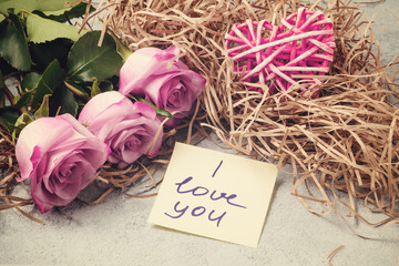 bouquet of pink roses, a heart and a note with the inscription I love you on the table-the concept of love and care
